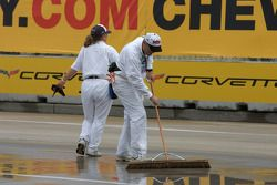 Corner workers sweep the puddles of water