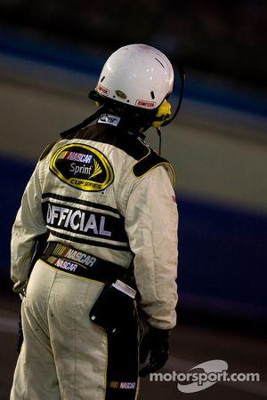 Un officiel de la NASCAR attend sur la piste durant un avertissement
