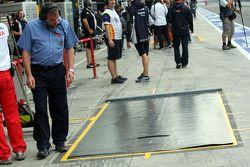 Une bâche spéciale contre la pluie placée devant le garage Toyota, au niveau de l'arrêt aux stands