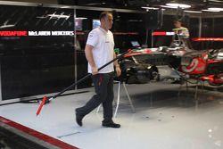 Les équipiers McLaren Mercedes nettoient l'eau du garage après les fortes pluies