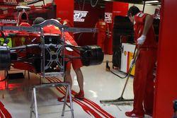 Les équipiers Scuderia Ferrari nettoient l'eau du garage après les fortes pluies