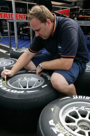 Un mécanicien Trident Racing marque les pneus Bridgestone