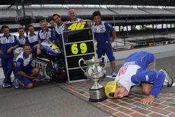 Race winner Valentino Rossi celebrates with Fiat Yamaha team members on the famous Yard of Bricks