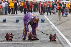 Les mécaniciens sèchent la voie des stands avant la course