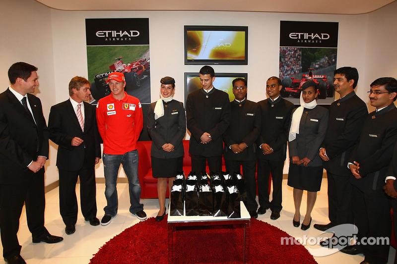 Kimi Raikkonen of Ferrari poses with Etihad staff at the opening of the Etihad Holiday Store at Mari