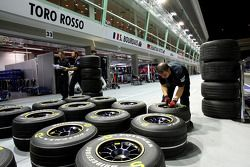 Scuderia Toro Rosso crew members with tyres in the pit lane