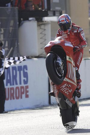 Casey Stoner takes the checkered flag to win the race