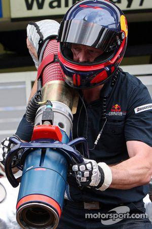 Un membre d'équipage Red Bull Racing avec l'injecteur de carburant pendant un entraînement aux stands