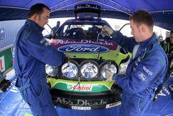 Les techniciens M-Sport attachent des phares à la Ford Focus RS WRC de Mikko Hirvonen etJarmo Lehtinen