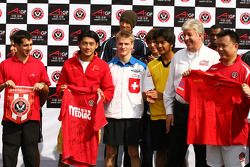 Ho Pin Tung, driver of A1 Team China hands over his team shirt for a football shirt