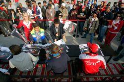 Hamad Al Fardan, Vitaly Petrov and Giedo Van der Garde sign autographs for race fans