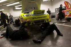 Yates Racing Ford crew members repair the demage on the car of Paul Menard