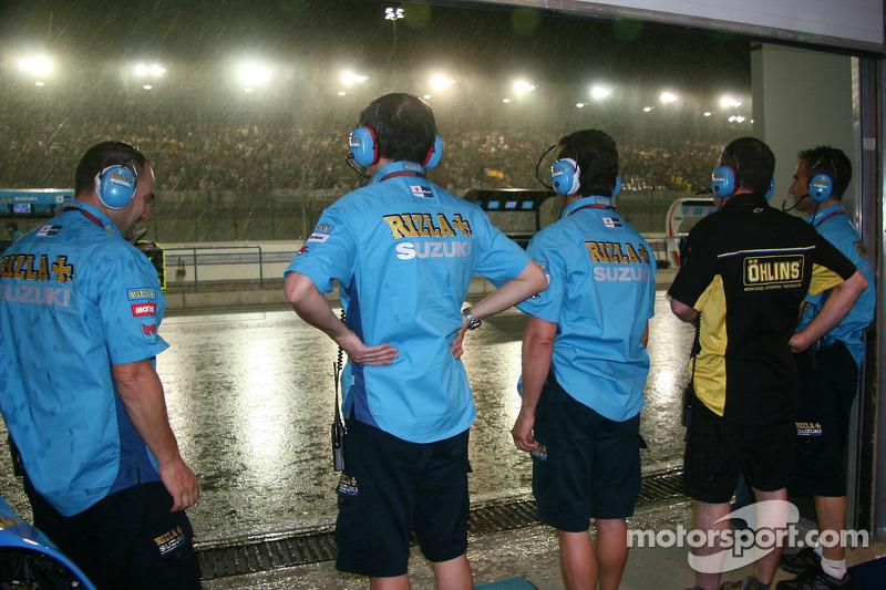Члены команды Rizla Suzuki MotoGP наблюдают за дождем