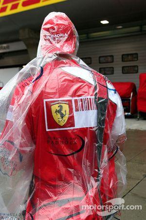 Un fan de Ferrari con la cubierta de la lluvia