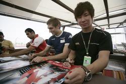 Kamui Kobayashi, Vitaly Petrov and Hamad Al Fardan sigh autographs
