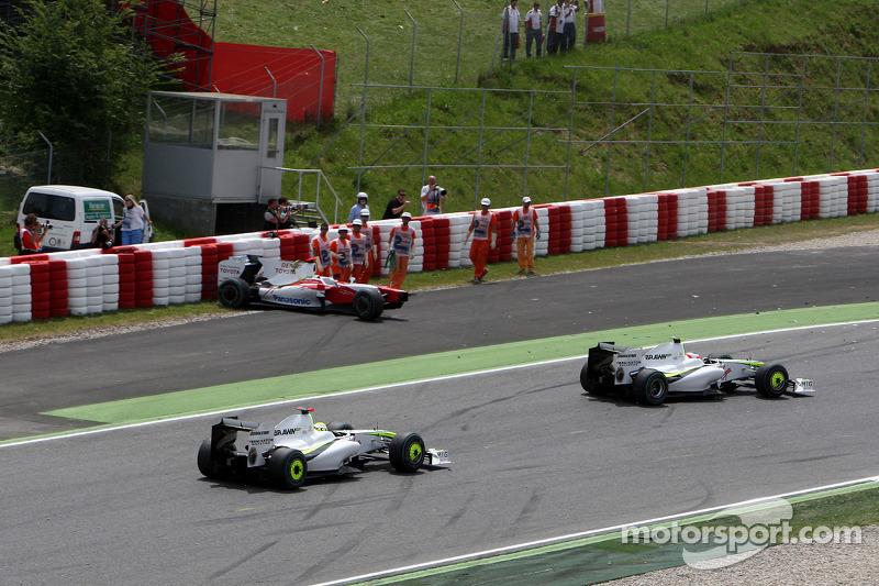 Rubens Barrichello, Brawn GP and Jenson Button, Brawn GP pass the crashed car of Jarno Trulli, Toyota F1 Team