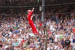 Race winner Helio Castroneves climbs the fence