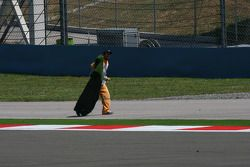 Les commissaires enlèvent le gazon du bord de la piste après qu'il soit venu sur la piste et ait causé un drapeau rouge.