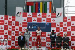 Pastor Maldonado celebrates his victory on the podium with Andreas Zuber and Karun Chandhok