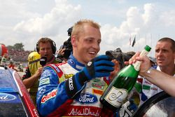 Winner Mikko Hirvonen is all smiles as he receives a bottle of champagne