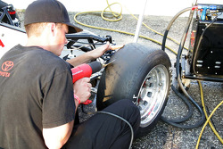 A crew member scrapes tires with a heat gun