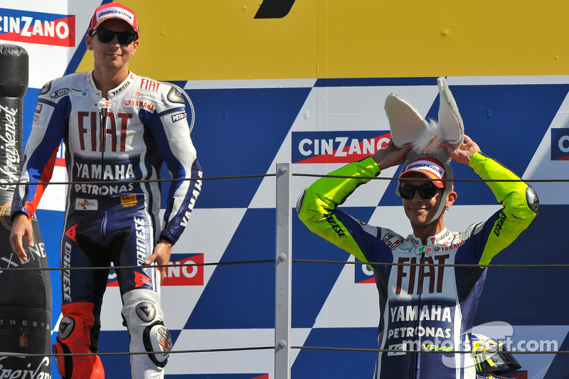 Podium: race winner Valentino Rossi, Fiat Yamaha Team with his donkey hat, and second place Jorge Lo