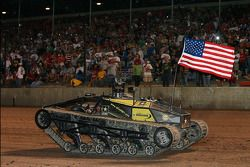 Darrell Waltrip drives a military tank along the front stretch