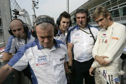 Vitaly Petrov regarde la course avec son équipe