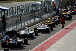 Cars line up in pit lane