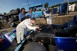 Robbie Pecorari works on the car while Adam Pecorari gets ready