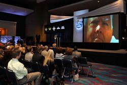 Guests and media view a video of NASCAR legend Junior Johnson following the announcement of being elected into the NASCAR Hall of Fame
