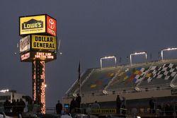 Lights illuminate empty grandstands after rain delayed practice