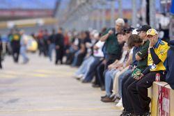 Les membres d'équipage et les fans sont assis le long du mur des stands lors des qualifications