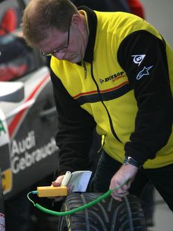 Tyre technician measures the temperatur on a DTM-tyre