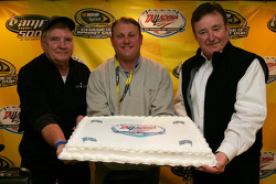Richard Brickhouse, first race winner at Talladega Superspeedway, Track President Rick Humphrey and team owner Richard Childress pose with a cake in the media center