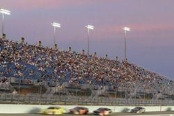 Cars pass the grandstand under a sunset