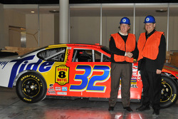 At HoF, Ricky Craven and car owner Cal Wells pose with the Pontiac Craven drove to victory at Darlington Raceway in 2003 in the closest finish ever in NASCAR racing