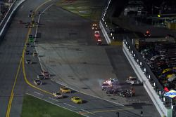 The field heads back to pit road while rescue team is at work on the car of Robby Gordon, Robby Gordon Motorsports Toyota