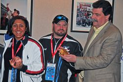 NASCAR president Mike Helton eyes gold medal of Olympic Bobsled driver Steve Holcomb with Alana Meyers holding her bronze medal for her success in the two-person bobsled run at Vancouver