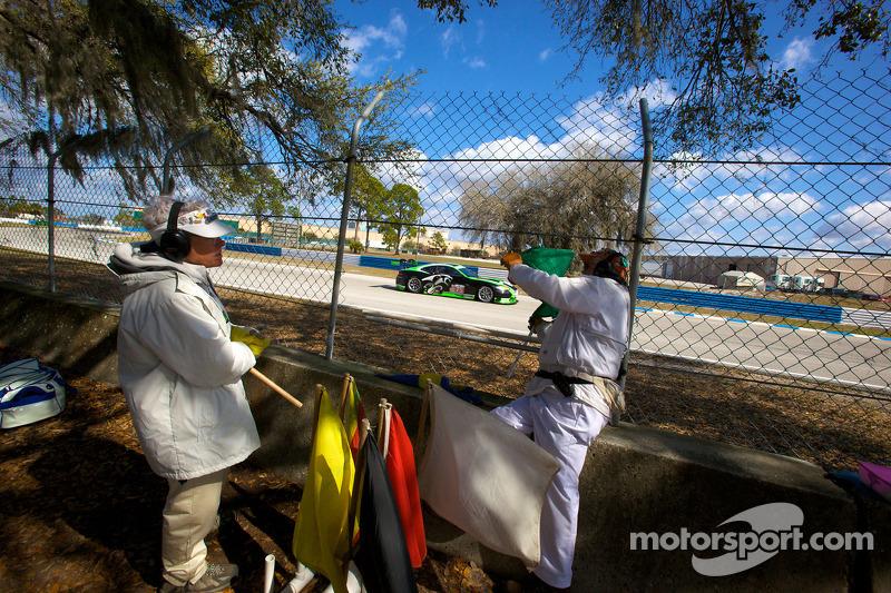 Marshalls aan het werk terwijl de #75 Jaguar RSR Jaguar XKRS: Paul Gentilozzi, Marc Goossens, Ryan Dalziel voorbij rijdt