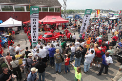 Fans watch a pit stop demonstration during pre race