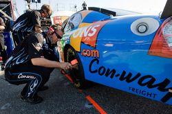 un membre d'équipes procède à des ajustement à la Coupons.com Ford