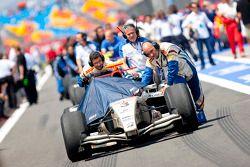 Giedo Van der Garde car is pushed into the pit lane