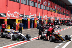 Formula Two cars wait in the pit lane
