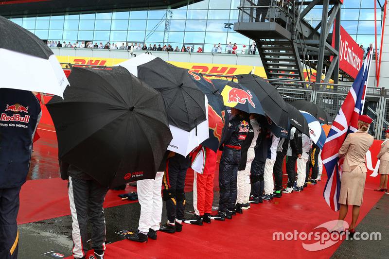 Nunca el 'God save the Queen' sonó tan británico, acompañado por la lluvia. Los pilotos tuvieron que refugiarse bajo los paraguas.
