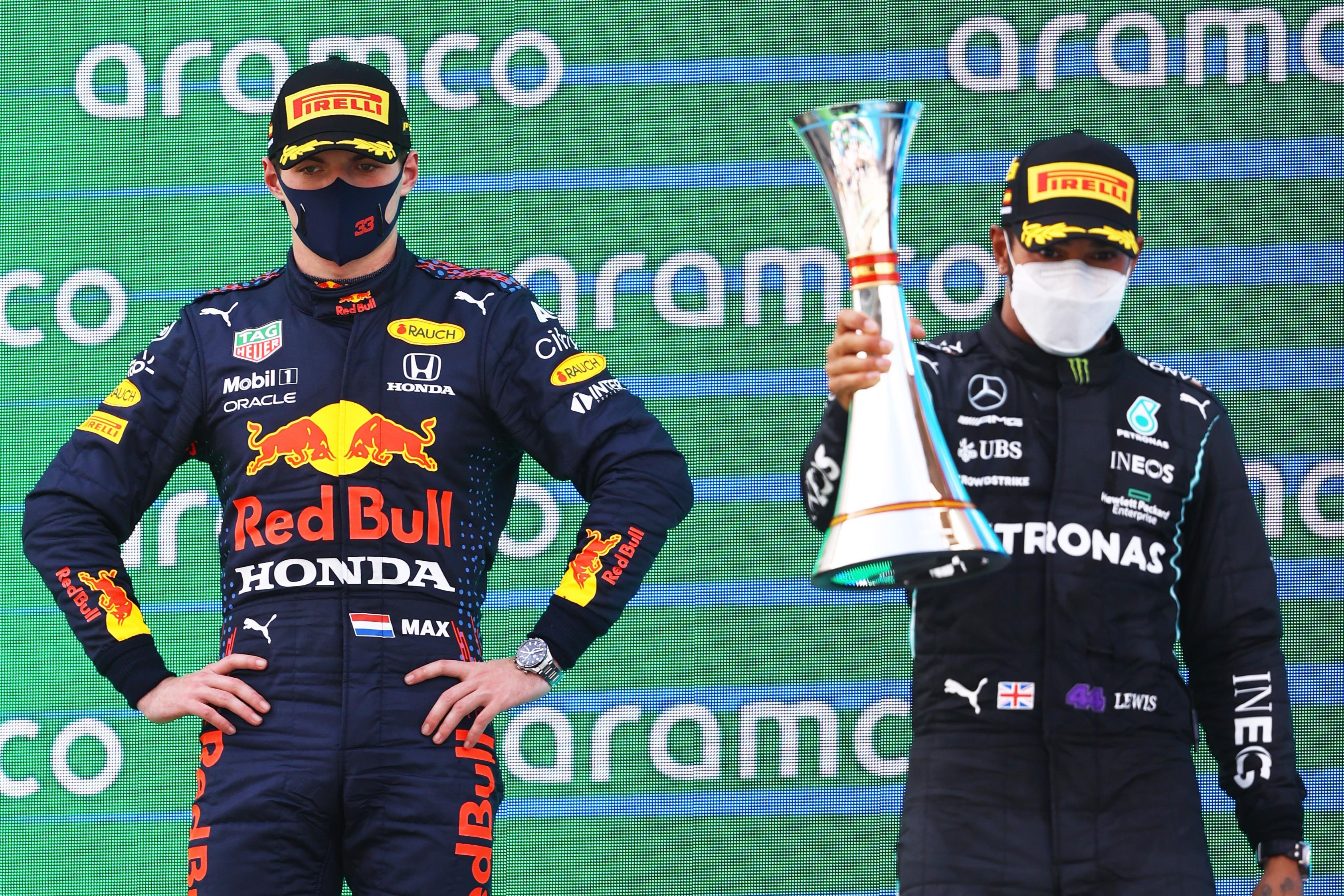 Verstappen looks on as Hamilton hoists his trophy