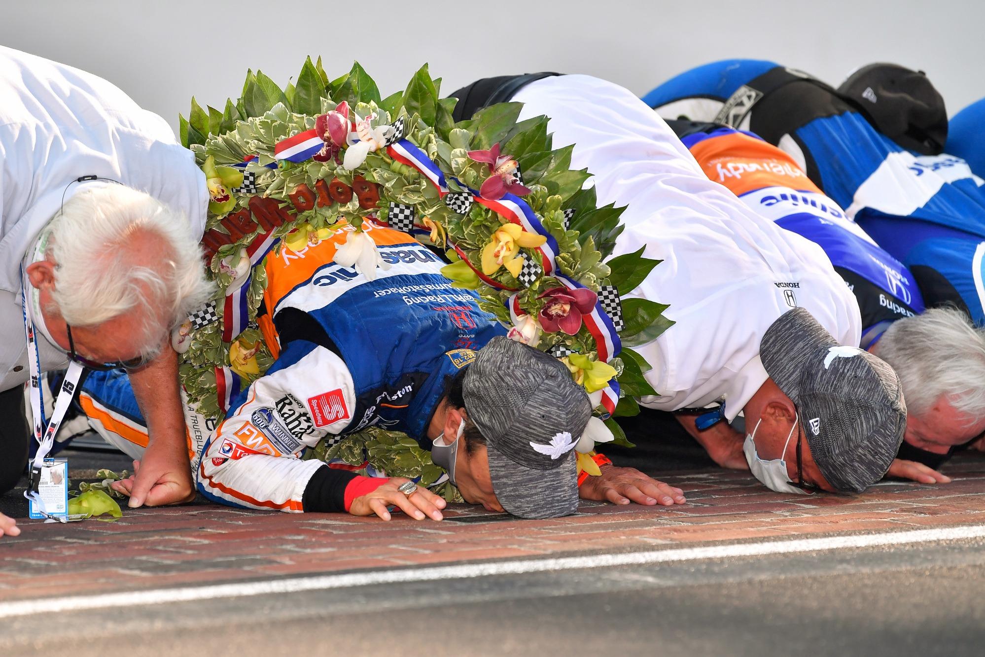 Takuma Sato and his RLL team kiss the bricks after winning the 2020 Indy 500