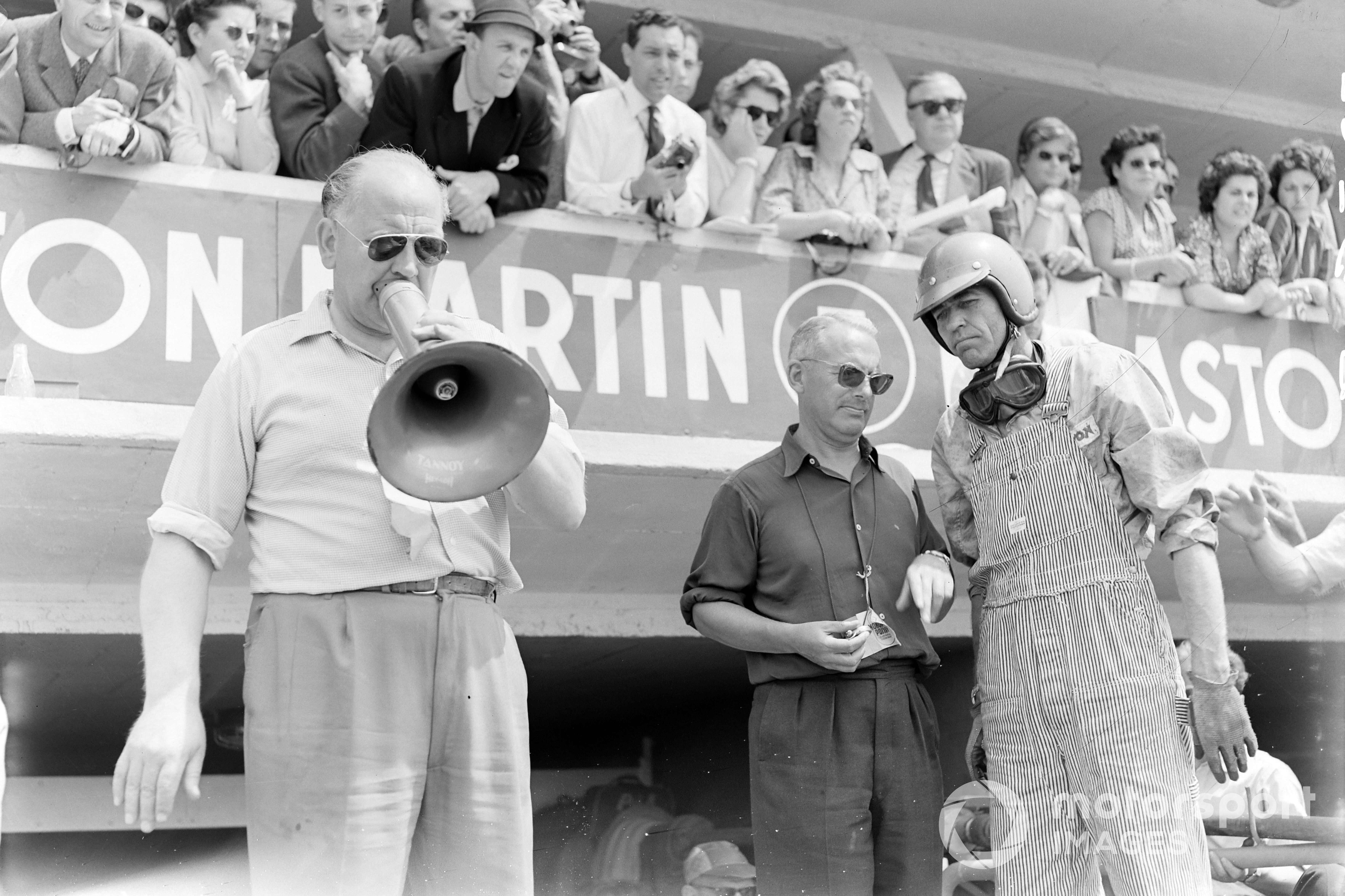Carroll Shelby (Aston Martin DBR1), 1st position, waits in the pits for the car to come in with Reg Parnell, on megaphone and Team Owner and Chief Designer, David Brown, 1959 Le Mans 24 Hours