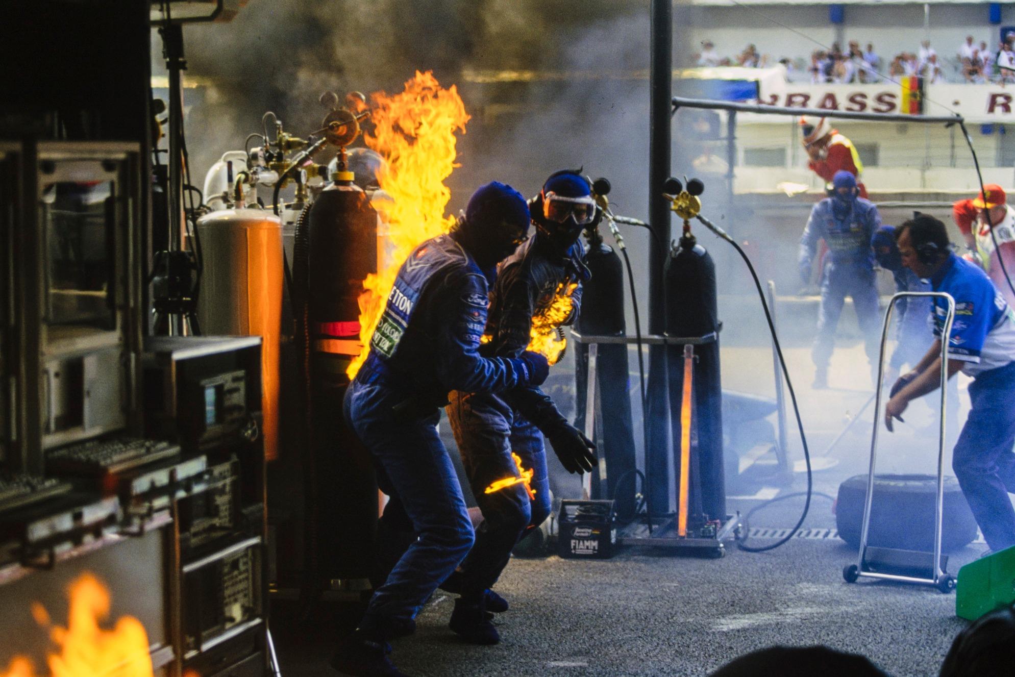 Still ablaze Benetton mechanics try to put out the fire