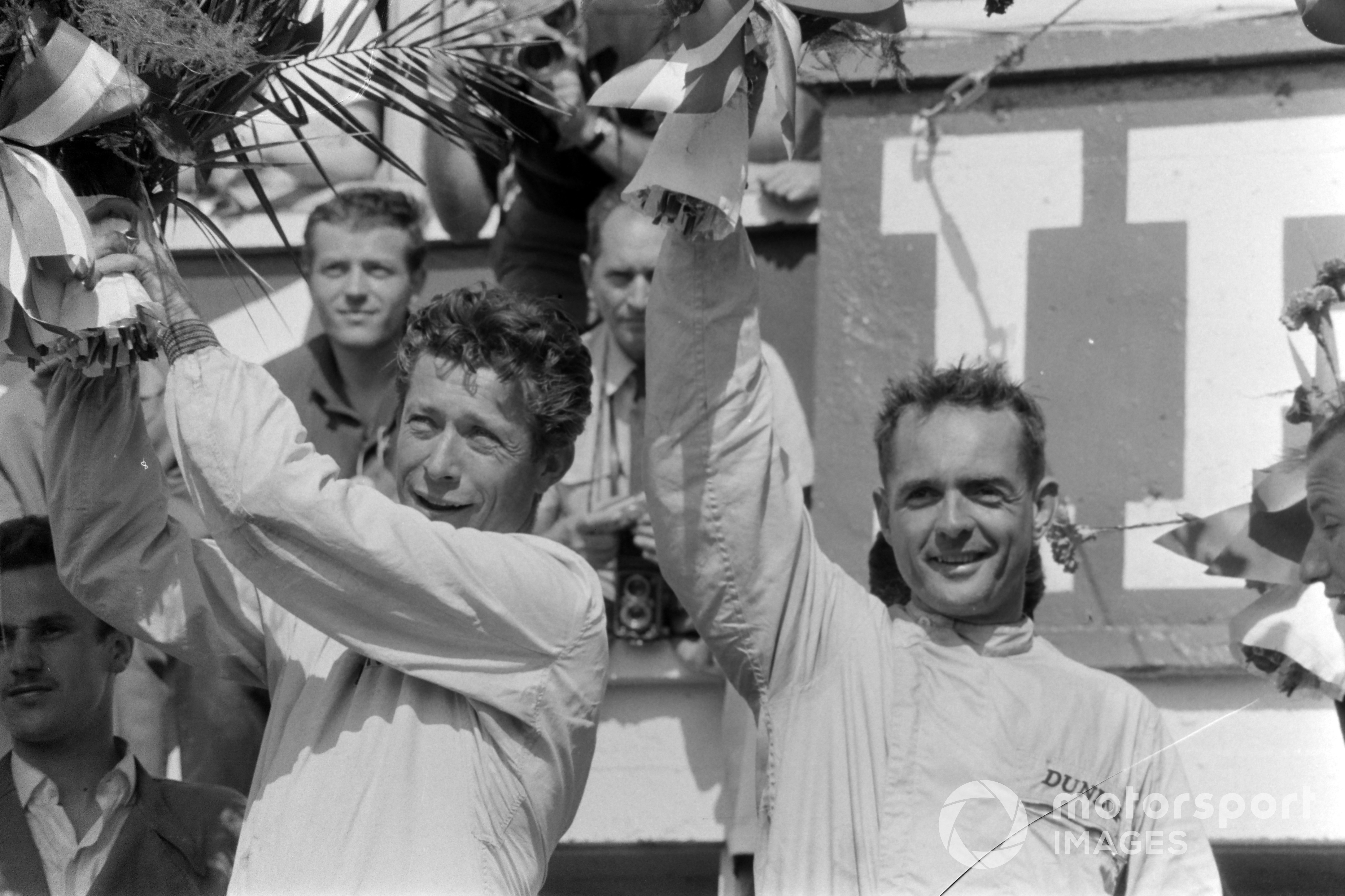 Olivier Gendebien and Phil Hill, 1st position, raise their bouquets on the podium at the 1962 Le Mans 24 Hours